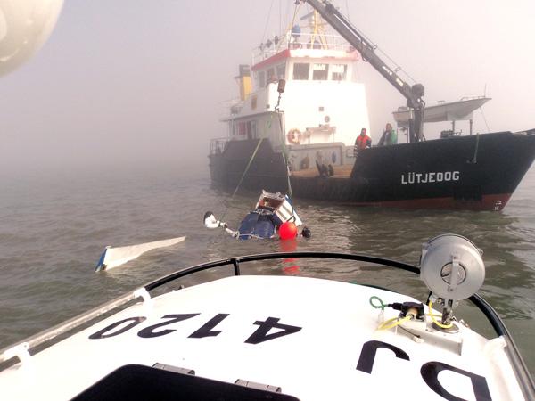 """Das Tochterboot JOHANN FIDI des Seenotkreuzers BERNHARD GRUBEN der DGzRS an dem ins Watt gestürzten Sportflugzeug. Im Hintergrund nähert sich der Tonnenleger """"Lütjeoog"""", um die Cessna zu bergen. (Foto: DGzRS/Die Seenotretter)"""