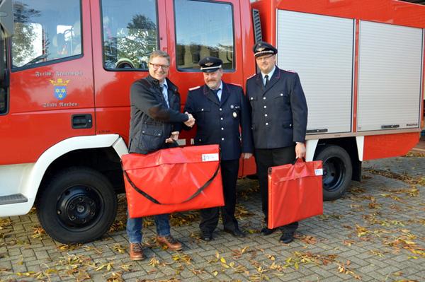 Wilfried Fick, Generalagent der R + V Versicherungsgruppe, bei der Übergabe zwei mobiler Rauchverschlüsse an die Norder Wehr. (Foto: M. Klaassen)