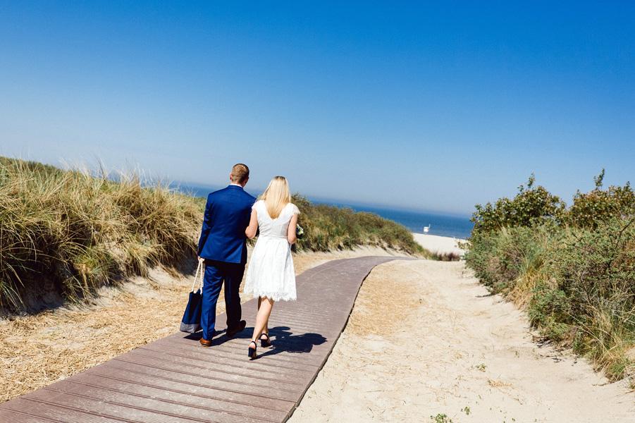 Hochzeitspaar auf dem Weg zum Strand.